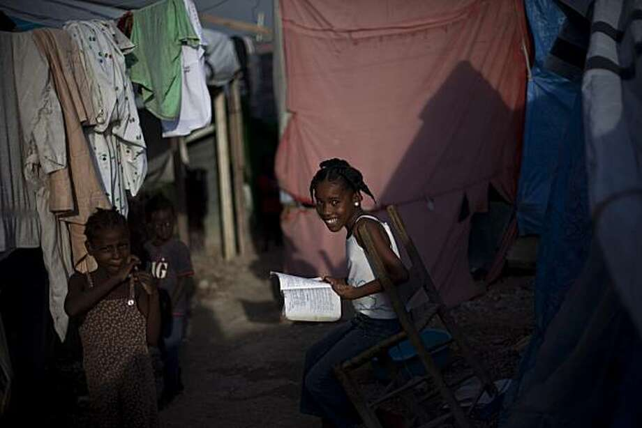 A girl smiles for pictures in a camp set up for people affected by the Jan. 12 earthquake in Port-au-Prince, Haiti, Wednesday, Aug. 4, 2010. Photo: Ramon Espinosa, AP