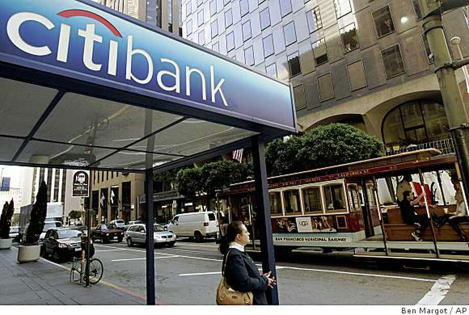 A cable car rolls past a Citibank branch office in San Francisco's financial district Monday, Nov. 17, 2008. Citigroup has announced it will cut 53,000 jobs from its massive payroll as it tries to slash costs, shed its riskier businesses and clear the debris of the housing bust. (AP Photo/Ben Margot) Photo: Ben Margot, AP