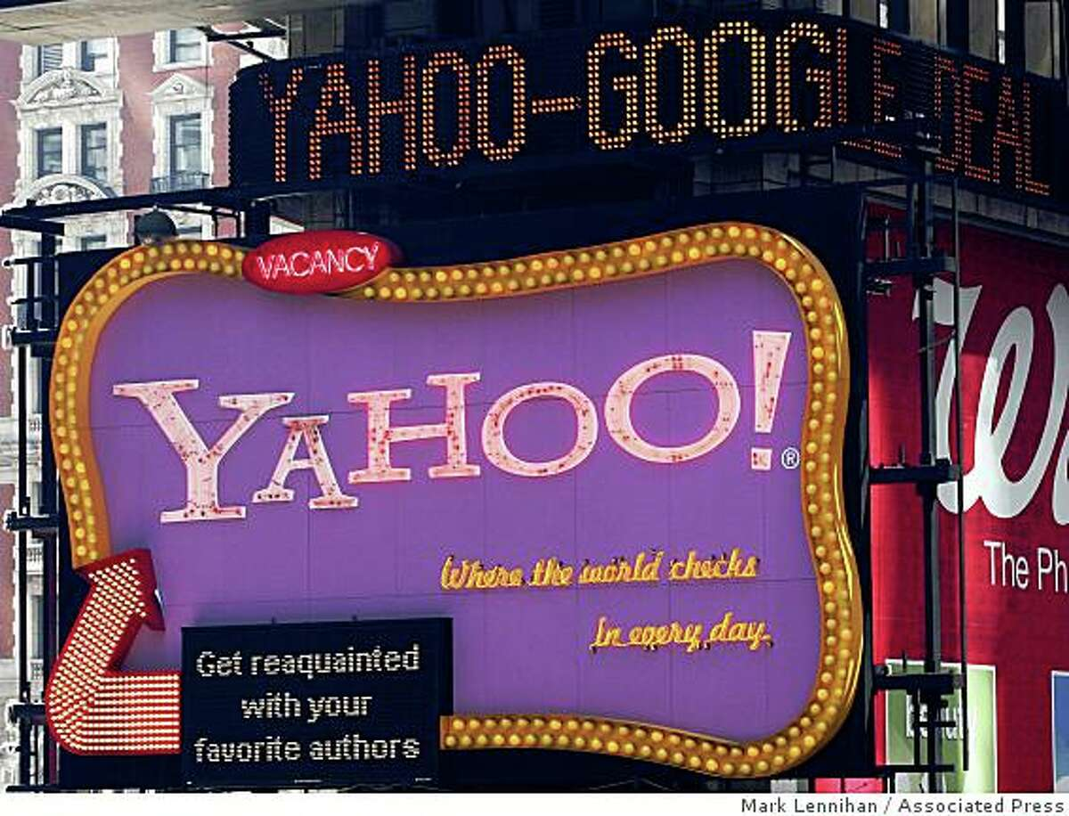 A news ticker carries headlines about Yahoo and Google above a Yahoo billboard on Thursday, April 17, 2008 in New York's Times Square. Microsoft Corp. has yet to convince Yahoo Inc. to agree to a friendly takeover. Yahoo may pursue an advertising alliance with Google Inc. that could lead to a long-term partnership. (AP Photo/Mark Lennihan)