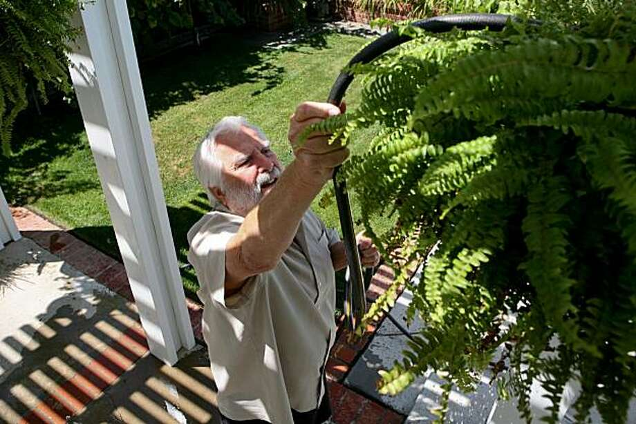 Lynn Rhynes demonstrates his range of motion as he waters ferns hanging from the patio cover in the backyard of his home on Friday, August 6, 2010 in San Jose, Calif.  Rhynes underwent joint surgery on both his shoulders and his left knee due to severe arthritis beginning five years ago and now enjoys a pain free life. Photo: John Sebastian Russo, The Chronicle