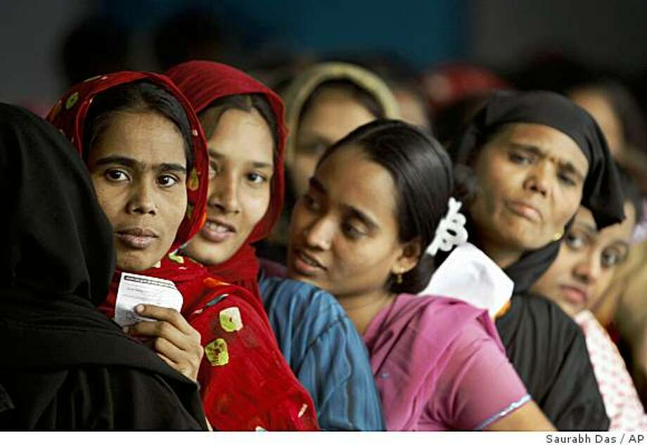 Women stand in a queue to cast their votes for the general elections in Dhaka, Bangladesh, Monday, Dec. 29, 2008. Security forces lined the streets Monday as Bangladesh voted in its first election in seven years, a much-anticipated poll that was to restore democracy to this troubled nation after two years of emergency rule. (AP Photo/Saurabh Das) Photo: Saurabh Das, AP
