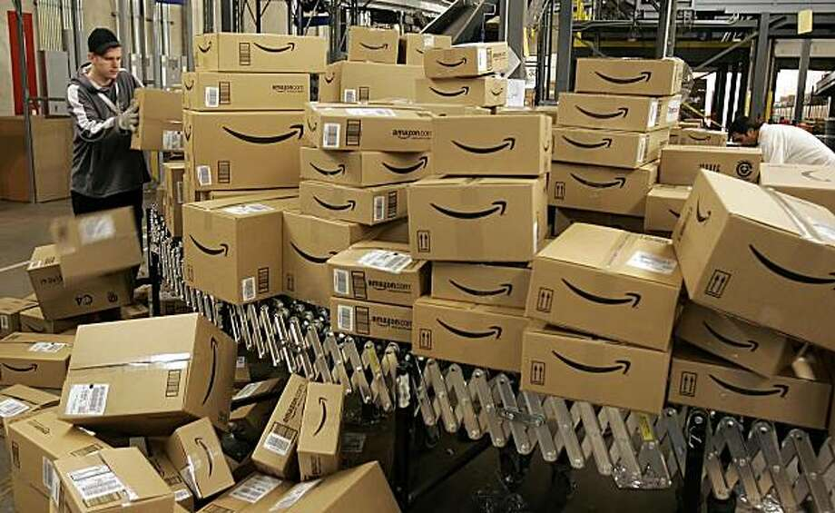 Amazon.com worker David Brendoff, left, moves boxes with merchandise for shipment Tuesday, Dec. 13, 2005, at the Amazon.com fulfillment center in Fernley, Nevada. With the holidays just around the corner, many shoppers are relying on online sites like Amazon.com to complete their shopping. This facility, over 800,000 sq. ft., or roughly 13 football fields, is capable of handling hundreds of thousands of orders per day. (AP Photo/Ben Margot) Photo: Ben Margot, AP