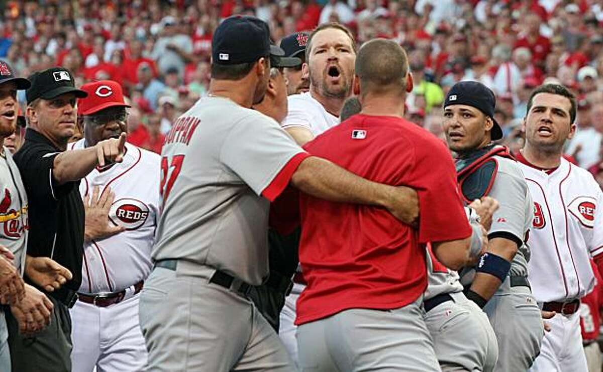 Cincinnati Reds Scott Rolen forth from right, yells at an unidentified St. Louis Cardinals player being held back by teammate Jeff Suppan while umpire Mark Wegner holds back Cincinnati Reds manager Dusty Baker, right, during an altercation in the first inning of their baseball game in Cincinnati Tuesday Aug. 10, 2010. Cardinals catcher Yadier Molina and Reds Joey Votto, far right, listen.