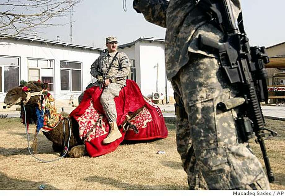 A U.S. soldier sits on a camel hired for an event marking the Christmas day at a U.S. base in Kabul, Afghanistan on Thursday, Dec. 25, 2008. (AP Photo/Musadeq Sadeq) Photo: Musadeq Sadeq, AP