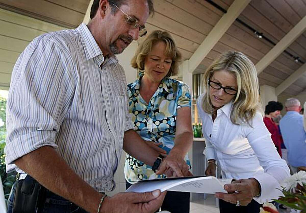 Scott Victor, Kelly Martin and Jaina Maier look at mementos at a reunion of former student singers and their third grade teacher Rita Abrams in Mill Valley, Calif., on Thursday, July 15, 2010, who together recorded a surprise hit song about their hometown of Mill Valley 40 years ago.