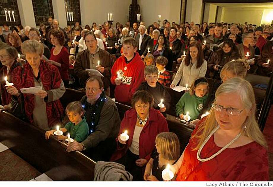 Hundreds of people gather at The First Unitarian Universalist Church stand as they sing Silent Night and light candles at the  Christmas service, Wed. Dec. 24, 2008, in San Francisco, Calif. Photo: Lacy Atkins, The Chronicle