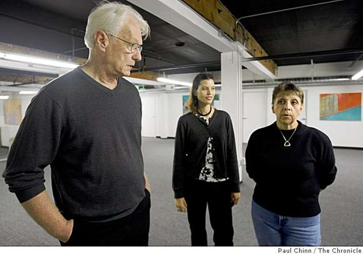 Artists Mark Ellinger and Patricia Araujo, center, visit with district manager Elaine Zamora, right, at the North of Market/Tenderloin Community Benefit District office in San Francisco, Calif., on Tuesday, Nov. 25, 2008. Ellinger, a photographer, and Araujo, a painter, have several of their artwork depiciting the Tenderloin neighborhood displayed at the office as part of the