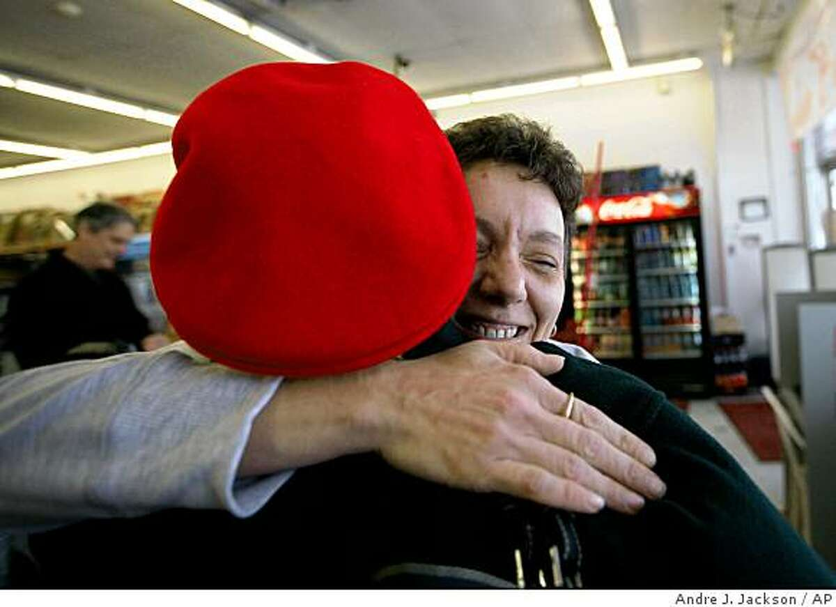 Lisa Machus, 37, a Dollar Store manager, hugs an anonymous secret Santa after receiving $100 in Lincoln Park, Mich. on Monday, Dec. 22, 2008. Machus plans to give the money to a deserving family. A Metro Detroit couple spent the day giving $11,000 to random working people to help make their Christmas better. The couple says they wanted to give money to people impacted by Detroit's struggling auto industry, poor economy, high unemployment and numerous home foreclosures. (AP Photo/Detroit Free-Press, Andre J. Jackson)