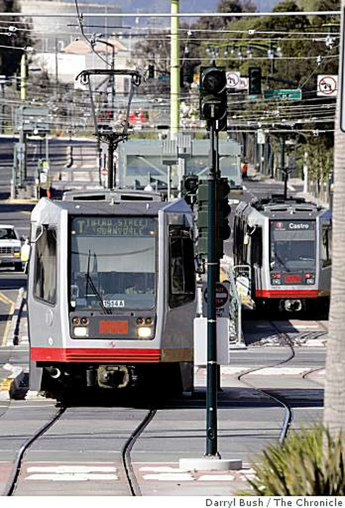 A MUNI streetcar heads North towards downtown near Jerrold Ave. as another streetcar, right, heads South on Third Street on the new T-Third streetcar line in San Francisco, CA,