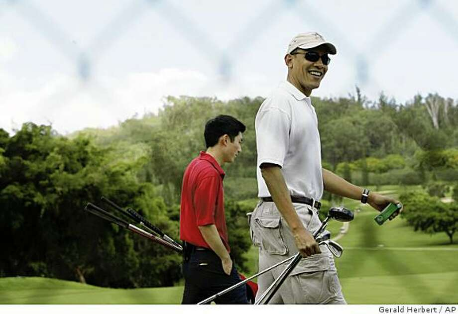 President-elect Barack Obama acknowledges the traveling press corps as he arrives to play golf in Kailua, Hawaii Sunday, Dec. 21, 2008.  Behind him is Eugene Kang, a member of Obama's staff. (AP Photo/Gerald Herbert) Photo: Gerald Herbert, AP