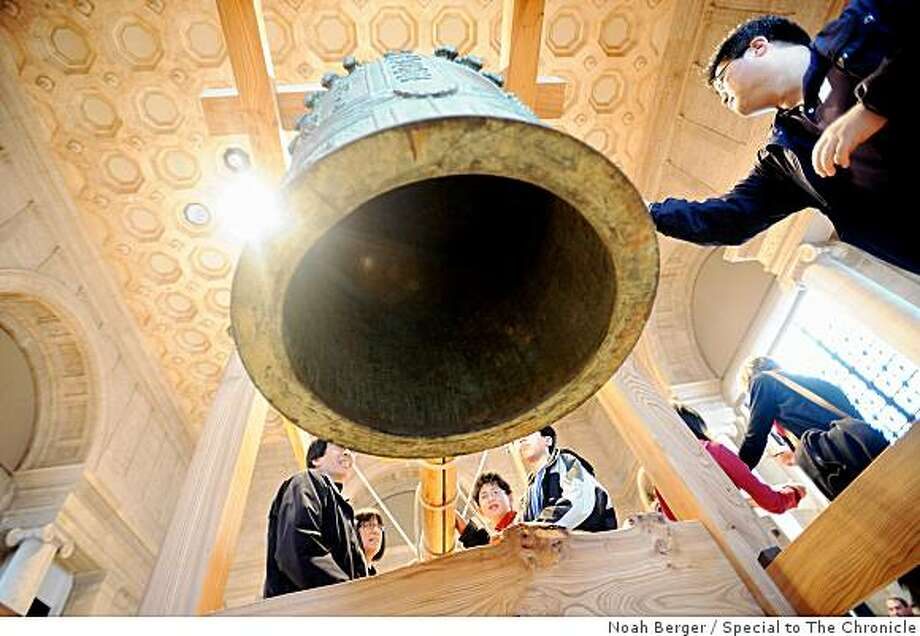 Visitors to the Asian Art Museum ring a bell as part of a New Year's celebration called Joya-no-kane on Wednesday, Dec. 31, 2008, in San Francisco. In Japan, the bell rings 108 times to relieve Buddhists of their sins. Several hundred people attended Wednesday's event and had a chance to ring the bell after Buddhist priest Gengo Akiba Roshi conducted a meditation. Photo: Noah Berger, Special To The Chronicle