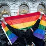 A man drapes himself with the rainbow flag in supporter of the overturning of Proposition 8 assemble at City Hall after marching down Market Street in San Francisco, Calif., on Wednesday, August 04, 2010.
