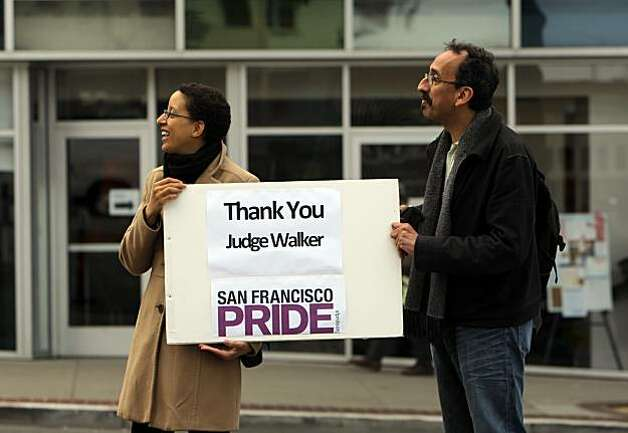 Amy Andre, Executive Director of San Francisco Pride, and Lucky Gutierrez, office manager for SF Pride, show their support to the marchers on Wednesday.  Supporters of same-sex marriage gathered in the Castro District of San Francisco, Calif., to celebrate a federal judge's ruling that Proposition 8 was unconstitutional and was  being struck down on Wednesday, August 4, 2010. Those gathered in the neighborhood then marched to City Hall for a rally celebrating the decision. Photo: Carlos Avila Gonzalez, The Chronicle