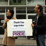 Amy Andre, Executive Director of San Francisco Pride, and Lucky Gutierrez, office manager for SF Pride, show their support to the marchers on Wednesday.  Supporters of same-sex marriage gathered in the Castro District of San Francisco, Calif., to celebrate a federal judge's ruling that Proposition 8 was unconstitutional and was  being struck down on Wednesday, August 4, 2010. Those gathered in the neighborhood then marched to City Hall for a rally celebrating the decision.