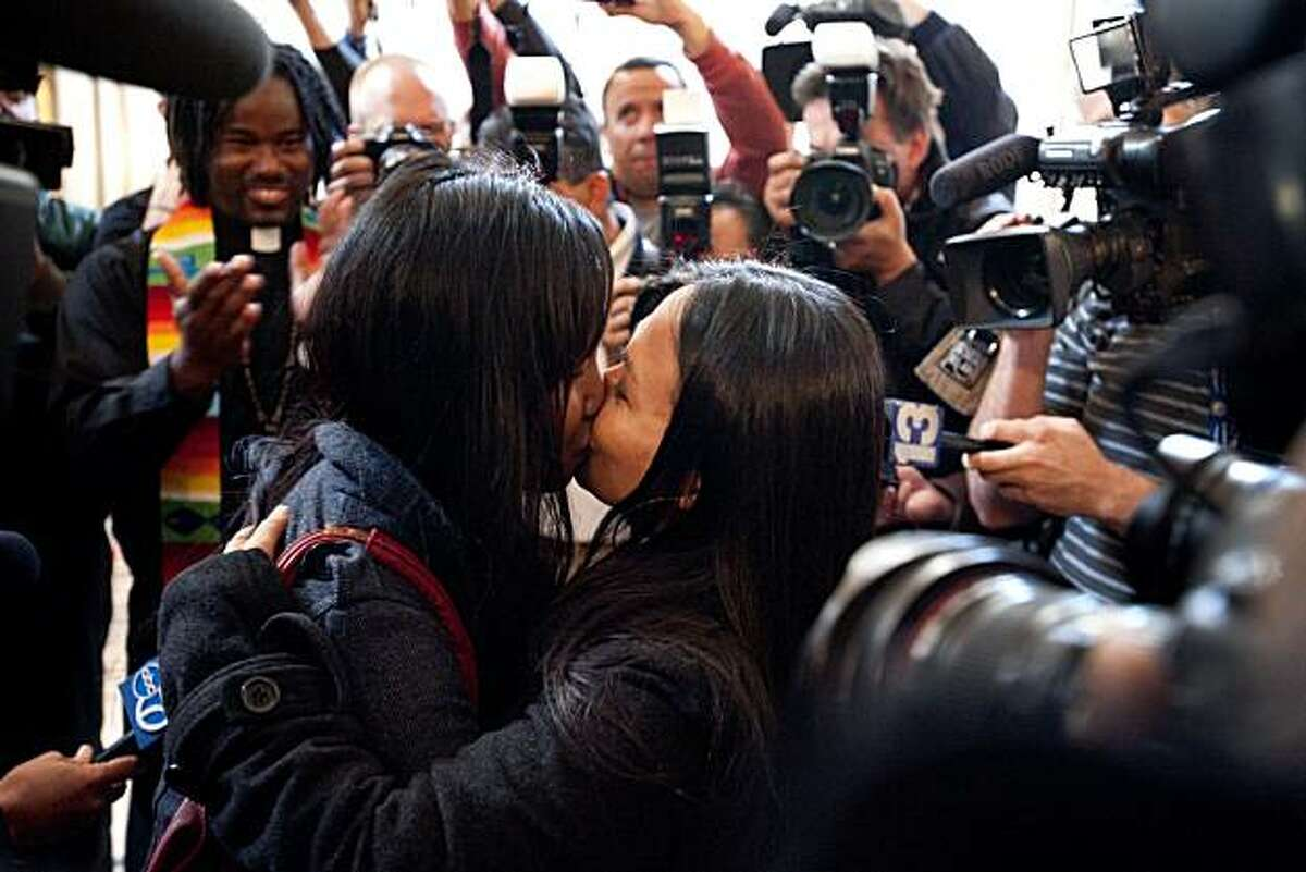 Vanessa Judicpa, 32 (left), and Maria Ydil, 31, both of San Francisco, Calif., give each other a kiss following their blessing ceremony by Rev. Roland Stringfellow (top left corner) after hearing about the overturning of Proposition 8 in San Francisco, Calif., on Wednesday, August 04, 2010.