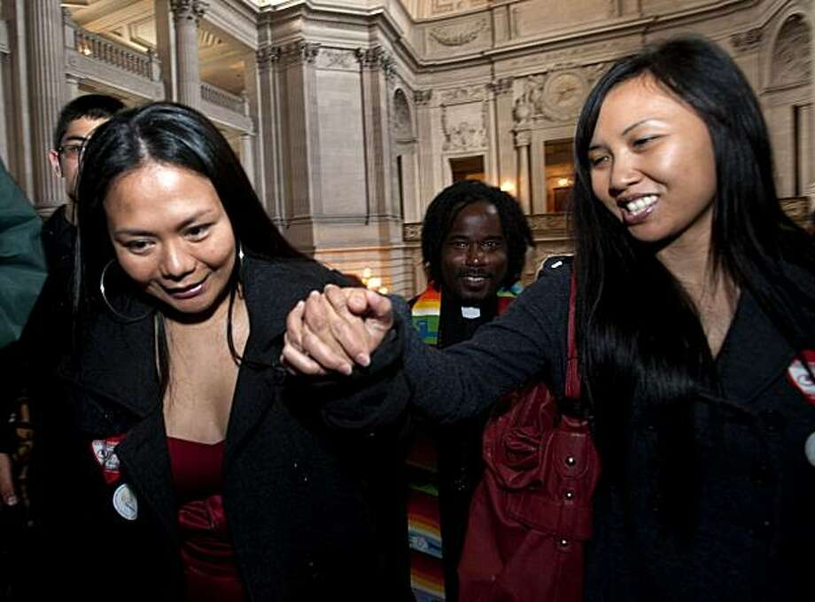 Vanessa Judicpa, 32 (right), and Maria Ydil, 31, both of San Francisco, Calif., make their way up the interior steps of City Hall to get a blessing on their union by Rev. Roland Stringfellow (center) after having their application for marriage put on hold following the overturning of Proposition 8 in San Francisco, Calif., on Wednesday, August 04, 2010. Photo: Chad Ziemendorf, The Chronicle