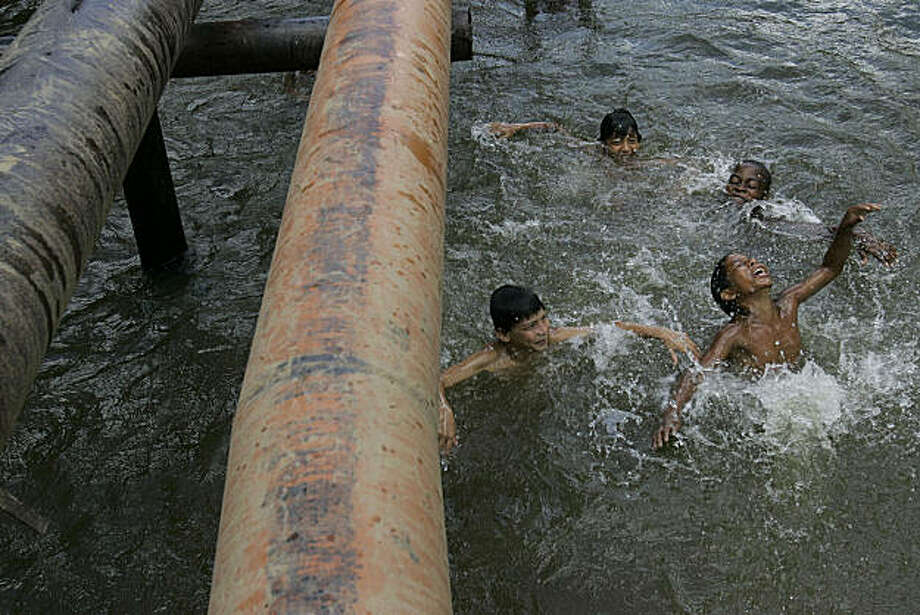 ** ADVANCE FOR SUNDAY, DEC. 21 ** Children play in a river where oil pipes run above the surface in Ecuador's Sucumbios province, Aug. 4, 2008.  Ecuador's President Rafael Correa has sided squarely with the 30,000 plaintiffs, Indians and colonists, in a class-action suit, dubbed an Amazon Chernobyl by environmentalists, over the slow poisoning of a Rhode Island-sized expanse of rainforest with millions of gallons of oil and billions more of toxic wastewater. (AP Photo/Dolores Ochoa) ** NO ONLN ** NO IONLN ** Photo: Dolores Ochoa, AP