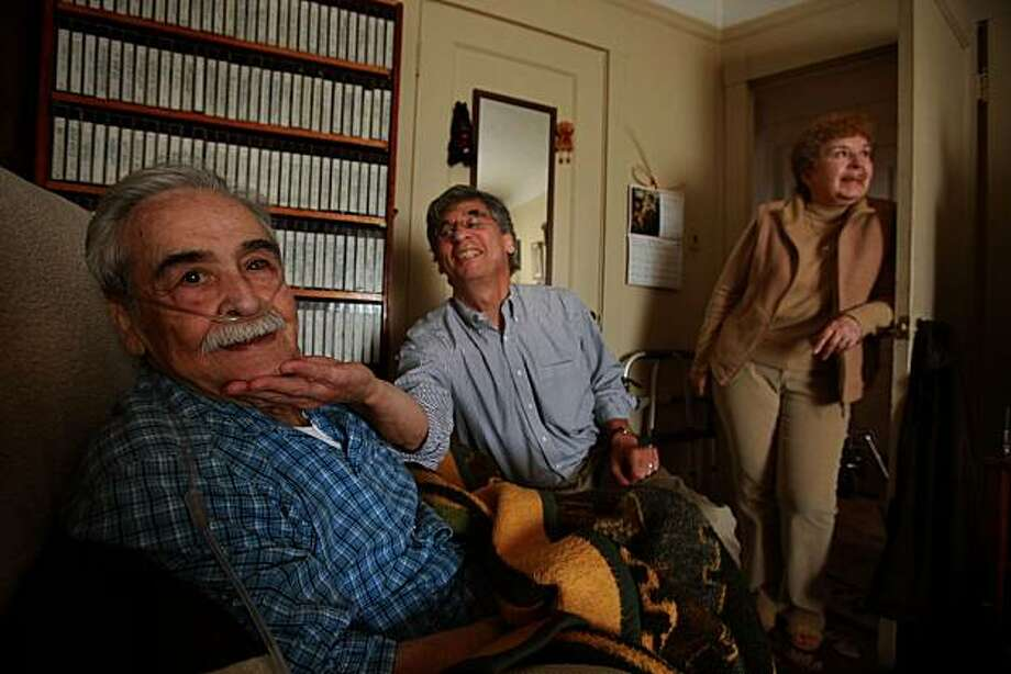 Hospice worker John Babbos (middle) plays with Jesus Pineda (left),  as he gets him to smile at home in San Francisco, Calif., on Monday, July 19, 2010. His wife Alicia Pineda says Babbos has been a great help, and is able to run errands and grocery shop while Jesus is being watched.  It is the 35th anniversary of Bay Area Hospice, the oldest hospice provider in the state. Photo: Liz Hafalia, The Chronicle