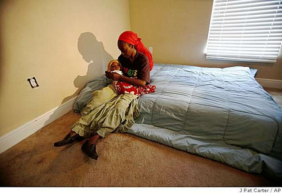 "Marie Nadine Pierre and her baby, Nennon, sit on a mattress in a ""people-less"" house Wednesday, Nov. 26, 2008 in Miami. She is squatting in a bank foreclosured house. (AP Photo/J Pat Carter) Photo: J Pat Carter, AP"