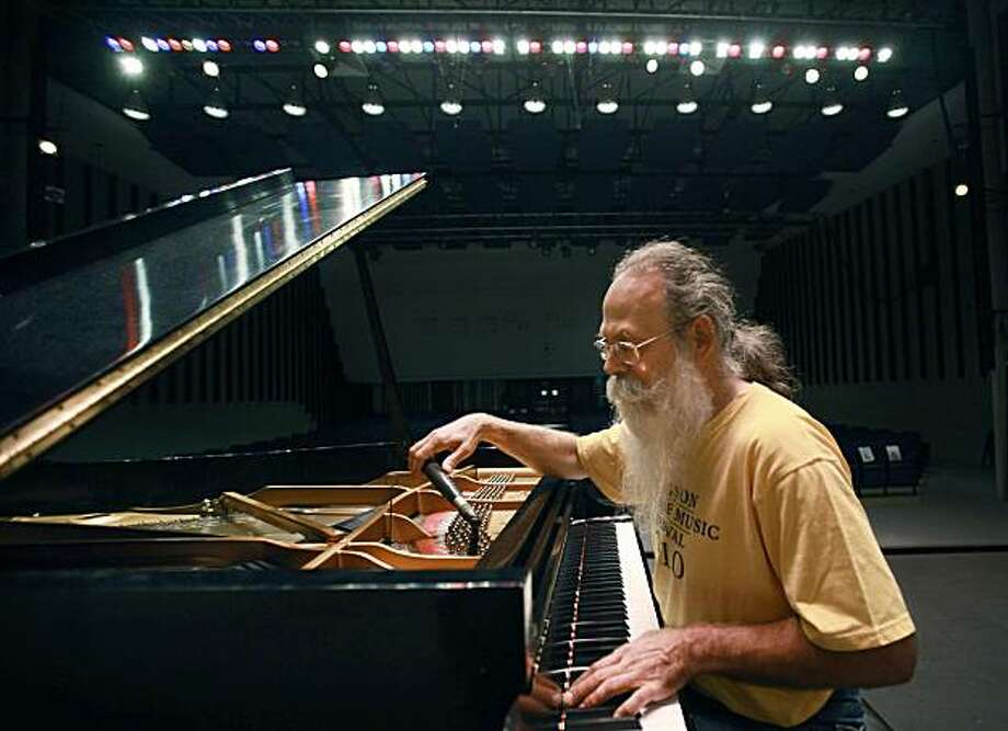 In this July 26, 2010 photo, piano tuner Bill Calhoun, who is marking his 25th anniversary this year as the piano tuner for the Newport Jazz Festival, tunes a piano in an empty concert hall on the campus of the University of Rhode Island, in South Kingston, R.I. Photo: Steven Senne, AP
