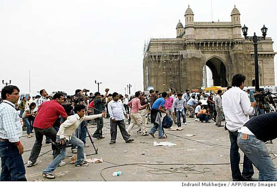 Journalists react in front of the historic Gateway to India monument as an unseen gunman fires shots towards them from inside the Taj Mahal hotel in Mumbai on November 28, 2008. The Indian military launched a grenade attack on a Mumbai hotel to flush out at least one militant who was holed up there after a hostage drama, an AFP photographer at the scene said. AFP PHOTO/Indranil MUKHERJEE (Photo credit should read INDRANIL MUKHERJEE/AFP/Getty Images) Photo: Indranil Mukherjee, AFP/Getty Images