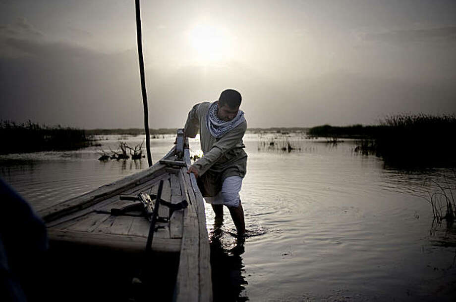 IRAQ MARSHES: Abbas Jassim al-Asadi, a fisherman and hunter who has spent most of his life in the marshes, pushes his boat from a shallow area of the marshlands. Illustrates IRAQ-MARSHES (category i), by Ernesto Londono (c) 2009, The Washington Post. Moved Saturday, July 25, 2009. (MUST CREDIT: Washington Post photo by Andrea Bruce.)    Abbas Jassim al-Asadi, a fisherman and hunter who has spent most of his life in the marshes, pushes his boat from a shallow area of the marshlands. Illustrates IRAQ-MARSHES (category i), by Ernesto Londono (c) 2009, The Washington Post. Moved Saturday, July 25, 2009. (MUST CREDIT: Washington Post photo by Andrea Bruce.) Photo: Andrea Bruce, Washington Post