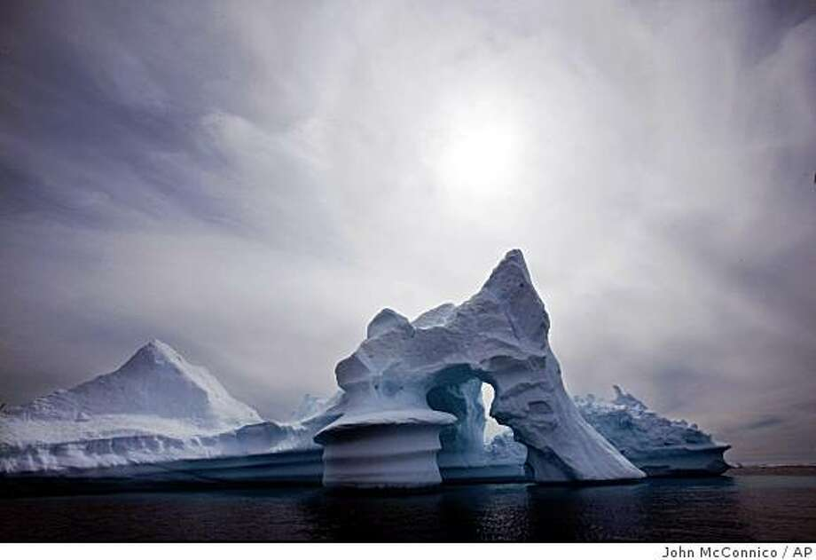 In this July 19, 2007 file photo, an iceberg melts off Ammassalik Island in Eastern Greenland.** FILE ** In this July 19, 2007 file photo, an iceberg melts off Ammassalik Island in Eastern Greenland. More than 2 trillion tons of land ice in Greenland, Antarctica and Alaska have melted since 2003, according to new NASA satellite data that show the latest signs of what scientists say is global warming. (AP Photo/John McConnico) Ran on: 12-17-2008 An iceberg melts off Greenland, which has suffered a major loss of land ice in the past five years, according to NASA satellite data. Ran on: 12-17-2008 Photo: John McConnico, AP