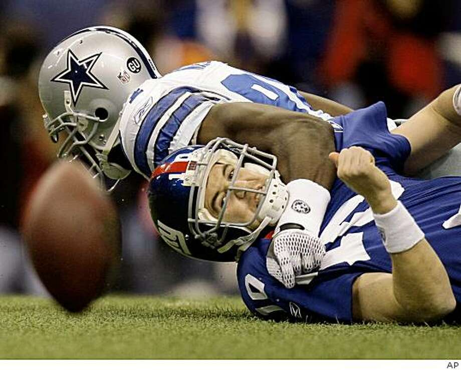 New York Giants quarterback Eli Manning (10) fumbles after he was sacked by Dallas Cowboys linebacker DeMarcus Ware (94) during the first quarter of an NFL football game Sunday, Dec. 14, 2008, in Irving, Texas. The Giants recovered the ball. (AP Photo) Photo: AP