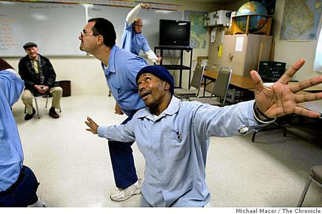 Alan Mandell (background, seated) watches actors in the San Quentin Drama Workshop, a group that Mandel founded in 1958 and is still going strong. Inmates Michael Willis, (front), John Neblett, (middle) and Erin O'connor, (back) run through some acting skills during a workshop on Friday Dec. 19, 2008. Photo: Michael Macor, The Chronicle