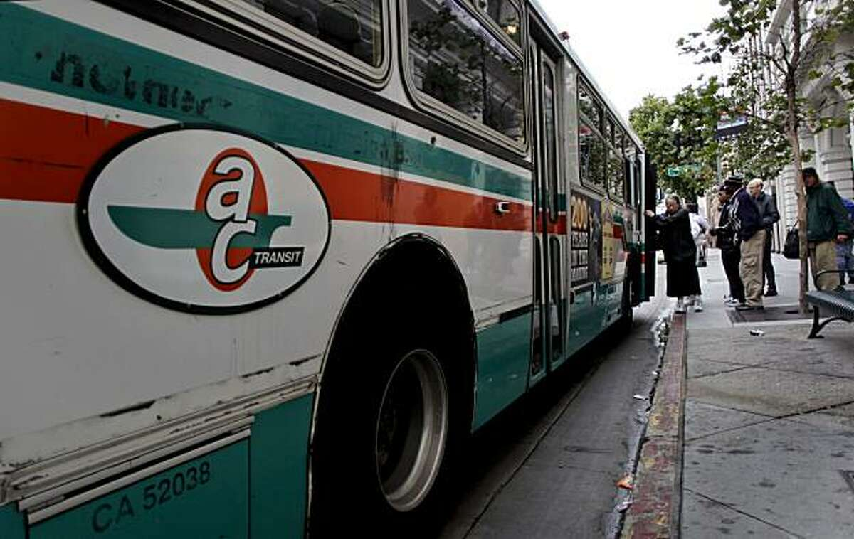 Riders board an AC Transit bus near the corner of Broadway and 14th Street in downtown Oakland on Friday.