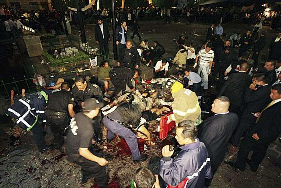 FILE - In this Sept. 15, 2008 file photo, police and rescue workers help injured people after assailants threw two grenades into a crowd of thousands of Independence Day revelers, killing eight and injuring more than 100 in Morelia, western Mexico. A federal judge has dismissed nearly all charges against the three men accused of the attack, who have spent nearly two years in jail and say they were beaten into false confessions. Photo: Anonymous, AP