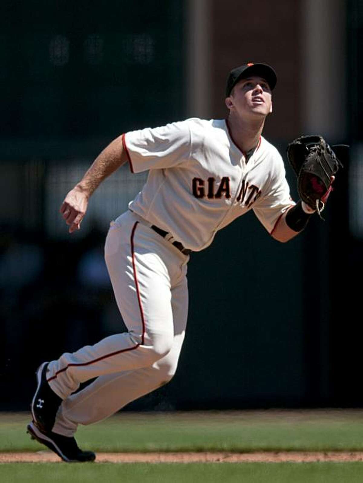 Buster Posey breaks hard to track a foul ball that he caught during the the Giants' 2-1 victory over the Los Angeles Dodgers in San Francisco on Saturday.
