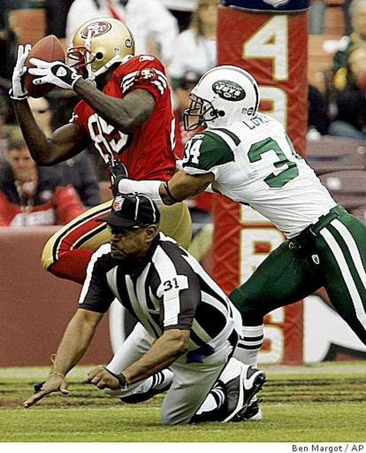 San Francisco 49ers' Vernon Davis, left, makes a reception past New York Jets' Dwight Lowery (34) as umpire Chad Brown (31) falls out of the way in the first half of an NFL football game Sunday, Dec. 7, 2008, in San Francisco. Davis fumbled the ball, which was picked up by 49ers' Joe Staley for a touchdown. (AP Photo/Ben Margot) Photo: Ben Margot, AP