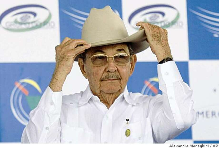 Cuba's President Raul Castro puts on the hat of Honduras's President Manuel Zelaya, unseen, during a summit of Latin American and Caribbean leaders in Costa do Sauipe, Brazil, Wednesday, Dec. 17, 2008. The two-day summit is aimed at strengthening political and economic ties in the region. (AP Photo/Alexandre Meneghini) Photo: Alexandre Meneghini, AP