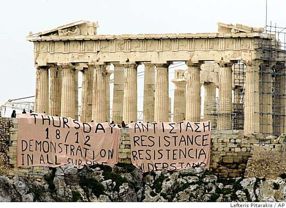 Backdropped by the ancient Parthenon, protesters can be seen after they placed giant banners off the Acropolis hill, in Athens, Wednesday Dec. 17, 2008.  Protesters in Greece have hung the two banners over the ancient monument's walls with slogans calling for mass demonstrations and 'resistance' after days of violent protest sparked by the fatal police shooting of a teenager in Athens.(AP Photo/Lefteris Pitarakis) Photo: Lefteris Pitarakis, AP