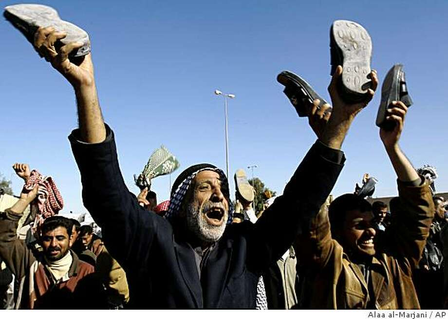 """Iraqis raise their shoes as hundreds demanded a release for  Iraqi journalist Muntadhar al-Zeidi who threw his shoes at US President George W. Bush, in Kufa, Iraq, Friday. Dec. 19, 2008. Al-Zeidi """"was beaten in the news conference and we will watch the tape and write an official letter asking for the names of those who assaulted him,"""" judge Dhia al-Kinani, the magistrate investigating the incident told The Associated Press. The journalist remained in custody and was expected to eventually face charges of insulting a foreign leader. A conviction could bring a sentence of two years in prison.  (AP Photo/Alaa al-Marjani) Photo: Alaa Al-Marjani, AP"""