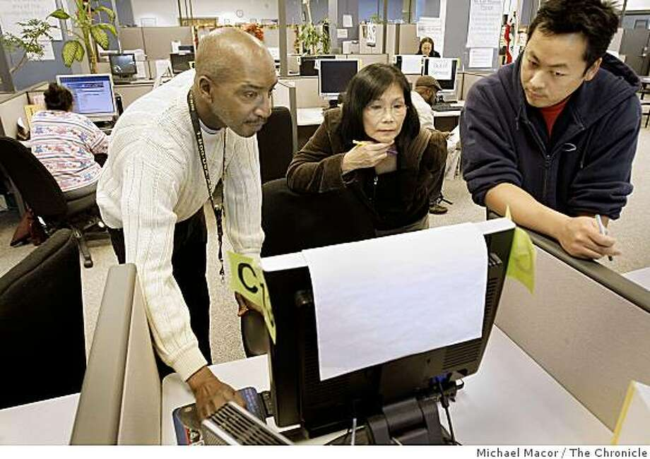 """Tommy Daughtrey, left, customer service representative, helps out Angel Lee and David Cho, right,  in use of the resoures at the  """"San Francisco Career Link"""" an employment assistance program, on Friday Nov. 7, 2007 in San Francisco, Calif.  Both are currentl looking for work. Administrators at the  program says they have seen an obvious increase of people coming in to use their resources. Photo: Michael Macor, The Chronicle"""