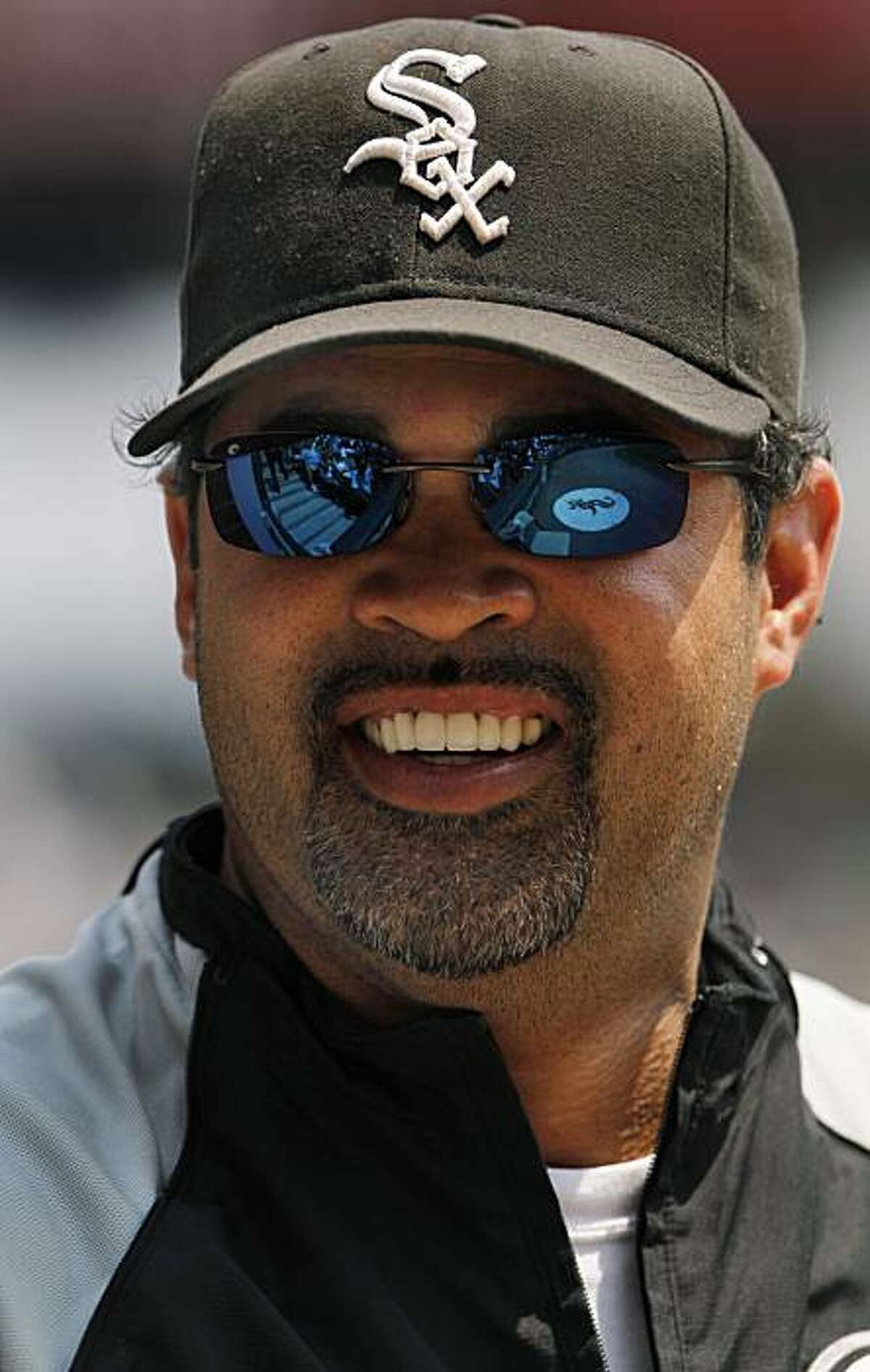 Chicago White Sox manager Ozzie Guillen talks with a player before a baseball game against the Oakland Athletics on Sunday, Aug. 1, 2010, in Chicago. The White Sox won 4-1.