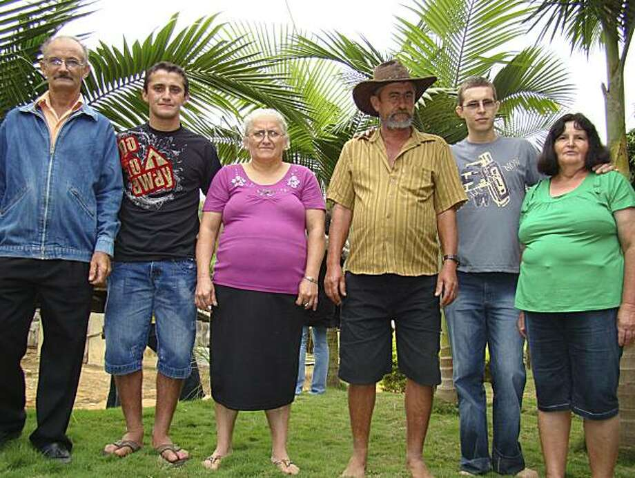 In this photo taken May 17, 2009, Dimas Jose Aliprandi, second from left left, and his parents, Antonio Paulino Aliprandi, left, and Zilda Maestrini Aliprandi, third from left, left, pose for pictures with  Elton Plaster, second from right, and his parents, Adelson Plaster, third from right, and Nilza Braun Plaster as they meet in Santa Maria de Jetiba, Espirito Santo state, Brazil. Aliprandi and Plaster, who had been switched at birth more than 20 years ago, are now living and working together with theirfamilies growing vegetables and coffee on a small farm in southeastern Brazil. Photo: Julio Huber, AP