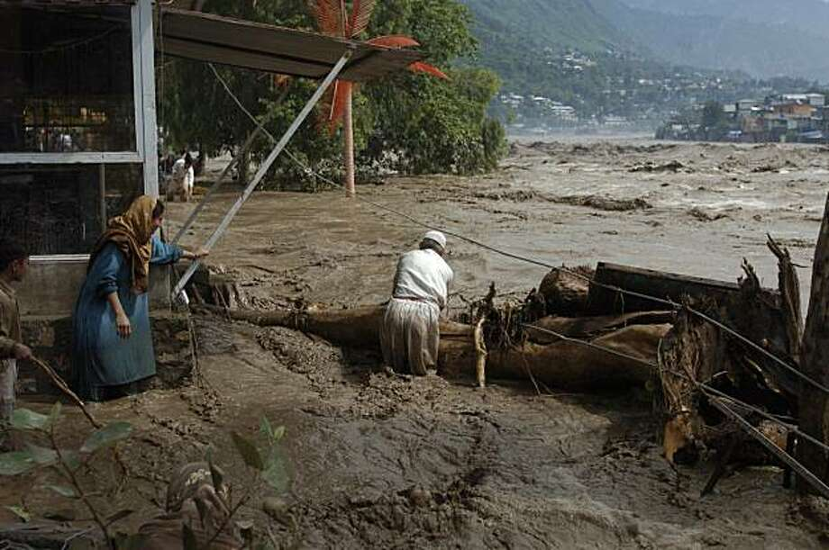 Pakistani villagers try to catch trees float in the flooded Nelum river in Muzaffarabad, the capital of Pakistani Kashmir on Friday, July 30, 2010. The death toll in three days of flooding in Pakistan reached more than 300 on Friday, rescue and government officials said, as rains bloated rivers, submerged villages, and triggered landslides.(AP Photo/Aftab Ahmed Photo: Aftab Ahmed, AP