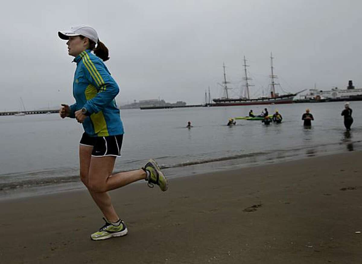 Robin Flynn runs past a group of bay swimmers Sunday July 18, 2010 at Aquatic Park in San Francisco, Calif. Robin Flynn, 27, is a soprano in the Merola Opera. She runs ten miles a day past Aquatic Park to stay in shape and help her prepare to perform.