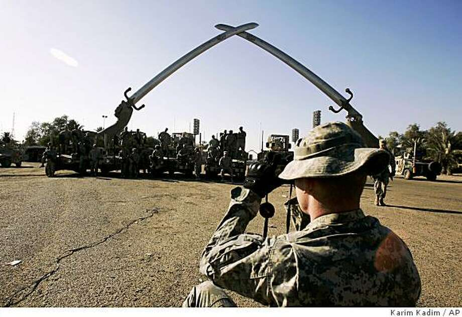 A soldier takes a picture of his unit in fron the the Crossed Sabers monument in Baghdad, Iraq, Thursday, Dec. 18, 2008. Late Iraqi dictator Saddam Hussein built this monument to symbolize Iraq's victory over Iran.  (AP Photo/Karim Kadim) Photo: Karim Kadim, AP