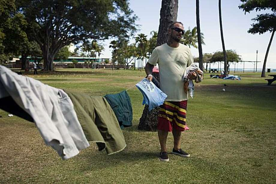 With the beach behind him, Tony Williams hangs his laundry between two palm trees in Waikiki, Monday, July 12, 2010 in Honolulu. Homelessness increased 15 percent on Oahu since last year according to a recent report.   A growing number of homeless are notfrom Hawaii but make the most of their situation by taking advantage of inviting beaches and support services.  State lawmakers are struggling with the visible problem of homelessness in tourist areas and some have proposed a contentious idea to use state money to fly the homeless back to wherever they came from.  William, originally from Long Beach, CA, took advantage of a similar program in New York City that flew him to Hawaii after he had a friend here pose as family  to take him in.   Williams sta Photo: Marco Garcia, AP