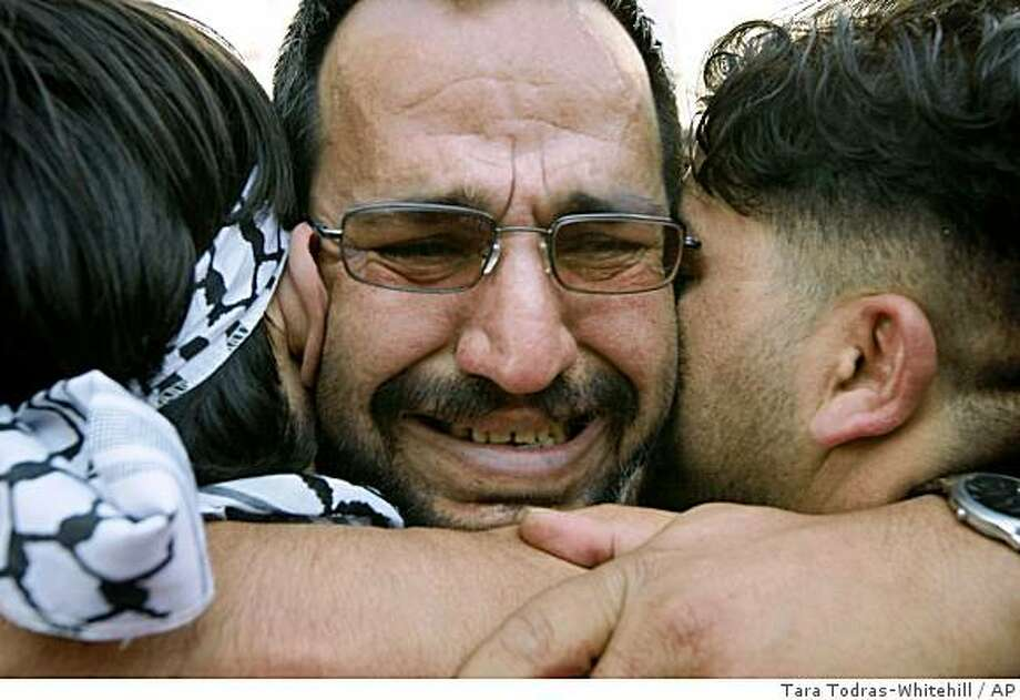 A released Palestinian prisoner is hugged by relatives, after arriving in the West Bank city of Ramallah, Monday, Dec. 15, 2008.  Israel released 224 Palestinian prisoners in a gesture to moderate Palestinian President Mahmoud Abbas. Israel holds more than 8,000 Palestinians, and their fate is an emotionally charged issue. Most Palestinians have had loved ones in prison and view the release of detainees as a test of Israel's willingness to make peace.(AP Photo/Tara Todras-Whitehill) Photo: Tara Todras-Whitehill, AP