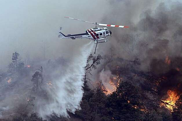 A fire helicopter drops water on the fire at Old West Ranch were residents were evacuated and about 30 to 40 homes have been lost to a wildfire about 10 miles southeast of the Mojave Desert town of Tehachapi, Calif. Wednesday, July 28, 2010. The area is about 70 miles north of Los Angeles. Photo: Alex Gallardo, AP