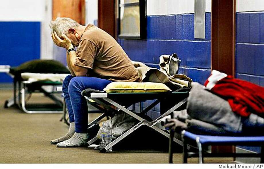 Russell French of Harrisville, N.H. sits on a cot at the storm shelter set up at the South Meadow School in Peterborough, N.H., on Friday, Dec. 19, 2008. Many are still waiting for power to be restored to their homes. (AP Photo/The Keene Sentinel, Michael Moore) Photo: Michael Moore, AP
