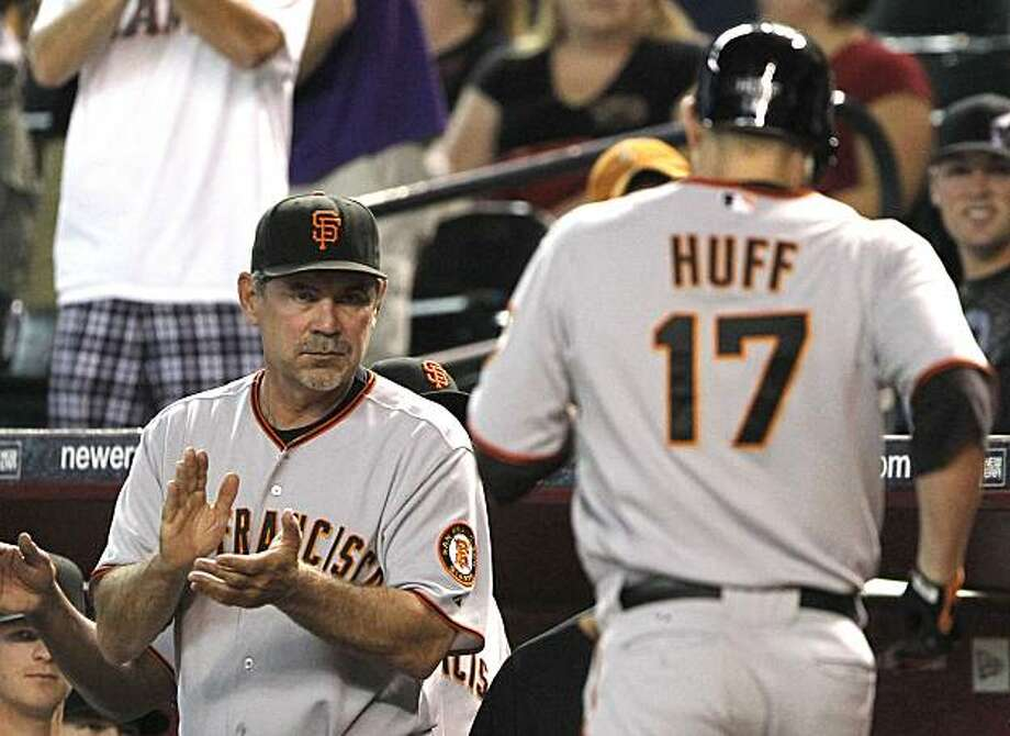 San Francisco Giants manager Bruce Bochy, left, claps for Aubrey Huff (17) after Huff hit a home run against the Arizona Diamondbacks in the first inning of a baseball game Friday, July 23, 2010, in Phoenix. Photo: Ross D. Franklin, AP