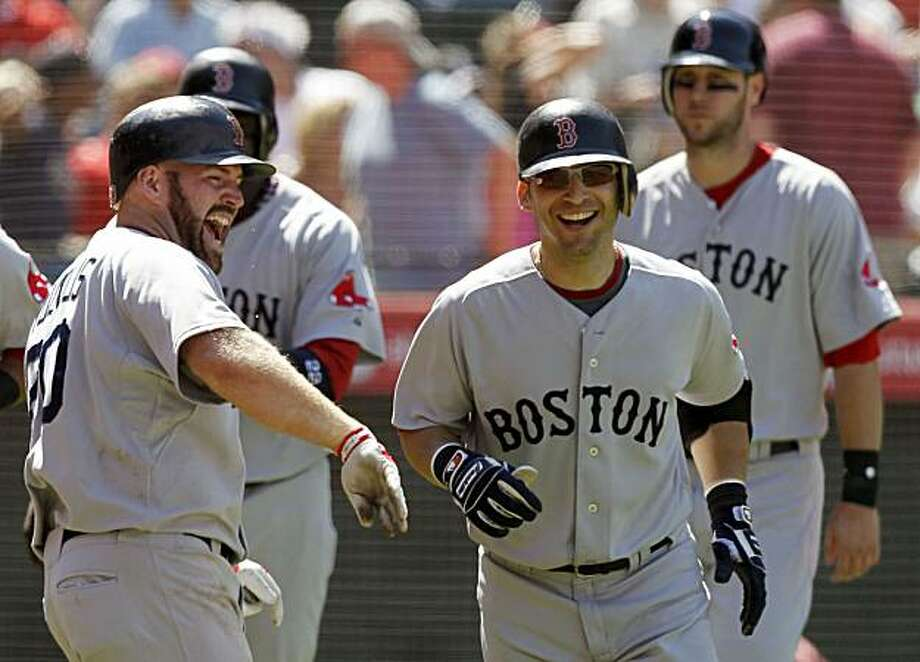 Boston Red Sox's Marco Scutaro, right, celebrates his grand slam with Kevin Youkilis, left, during the eighth inning of a baseball game against the Los Angeles Angels in Anaheim, Calif., Wednesday, July 28, 2010. Photo: Chris Carlson, AP