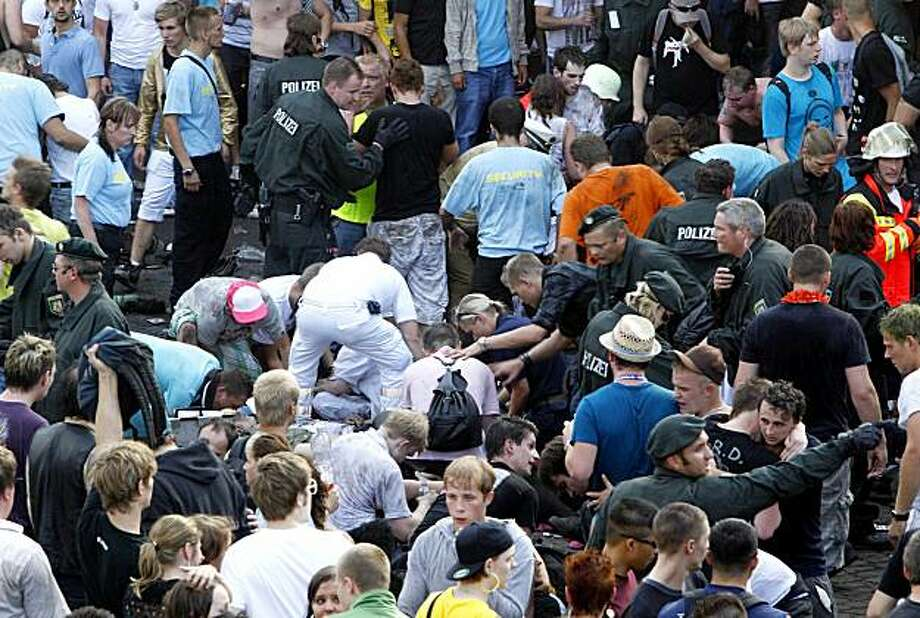 "** CORRECTION TO REMOVE SPECIFIC NUMBER OF PEOPLE KILLED ** Collapsed people get first aid after a panic on this year's techno-music festival ""Loveparade 2010"" in Duisburg, Germany, on Saturday, July 24, 2010. More than a dozen people were killed and others injured when mass panic broke out in a tunnel at the Love Parade. Photo: Hermann J. Knippertz, AP"