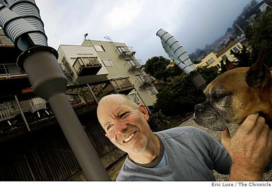 Chris Beaudoin and his dog Jet on the rooftop of  his garage are  two wind turbines of his Castro District home in San Francisco. Photo: Eric Luse, The Chronicle